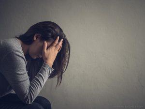 O erro foi do ex, o que fazer? Na imagem, uma mulher está sentada confusa passando as mãos pelo cabelo.